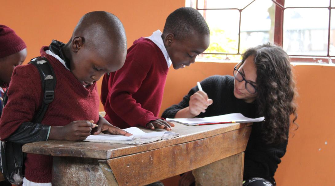 A volunteer teaching abroad helps children with their classwork in Tanzania.